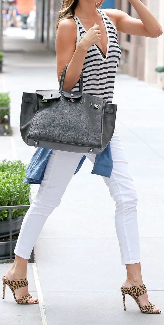 Miranda Kerr wears her skinny white jeans with high-heeled sandals, a blue denim shirt around her waste and an oversized tote.