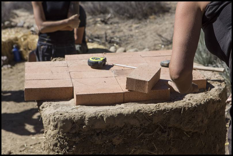 A layer of firebricks forms the floor of the oven. Here we fit them tight together on a bed of sand, trying to leave no cracks or crevices for ash to accumulate.  The fire will be built directly on this surface in the completed oven.