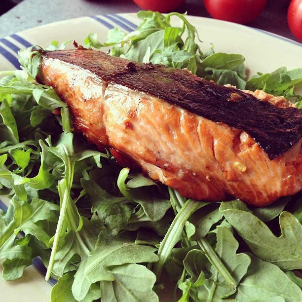 Baked salmon plated on top of arugula.