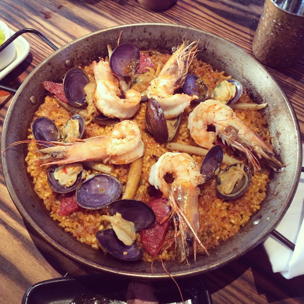 Paella the classic, made with bomba rice, jamón serrano-shellfish broth, caramelized root vegetables,chorizo, gulf prawns, clams, and lemon aioli