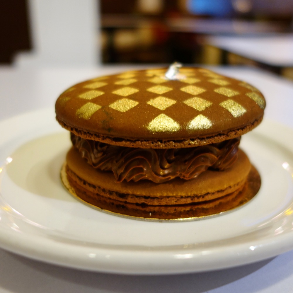 You wouldn't believe how amazing this giant chocolate passion fruit grand macaron was. When you cut into the shell layers, you'll discover a chocolate and passion fruit mousse and a white chocolate truffle with a melty passion fruit ganache in the middle. It is incredible. Does the 18k gold chessboard decoration look familiar? It is inspired by fashion icon Louis Vuitton.