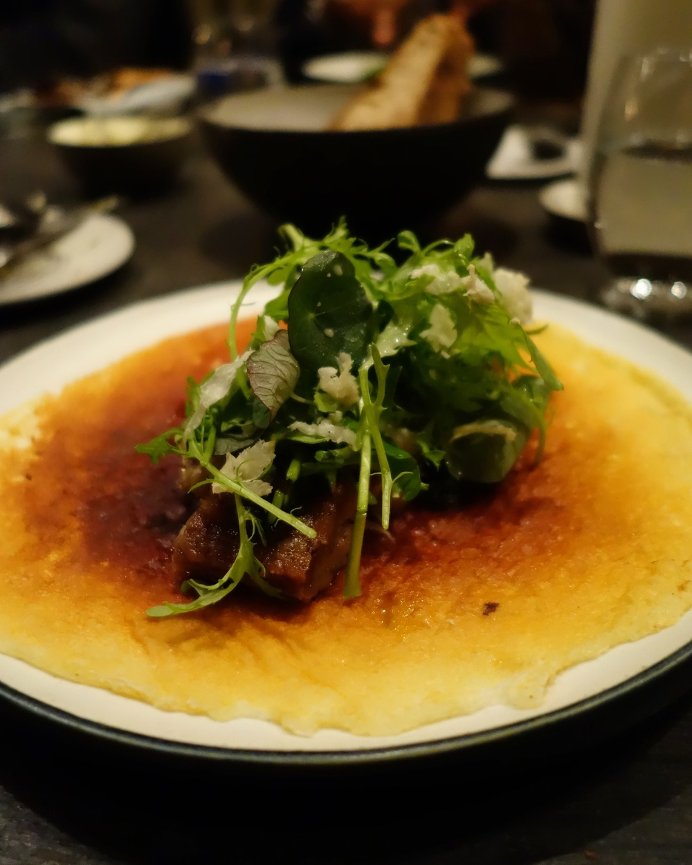 Caramelized milk skin with sautéed pigs tails and cress. The skin is made entirely from milk cooked in a pan. It's takes about 1 out of 10 tries to nail down the technique for the caramelization, which also involves spraying water in the process to prevent it from burning.