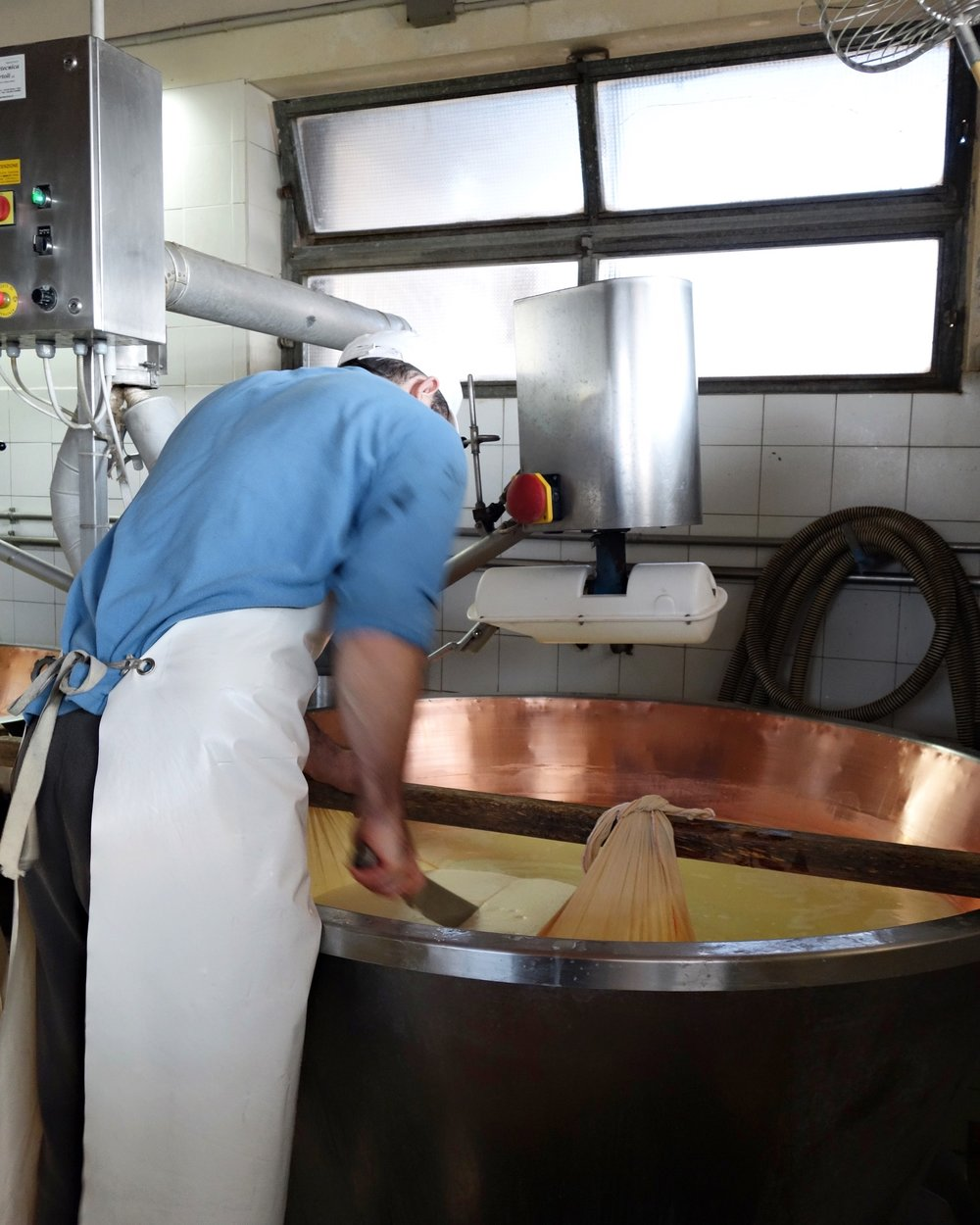 The cheese is cut in half.  Each half will produce one wheel of Parmigiano Reggiano.