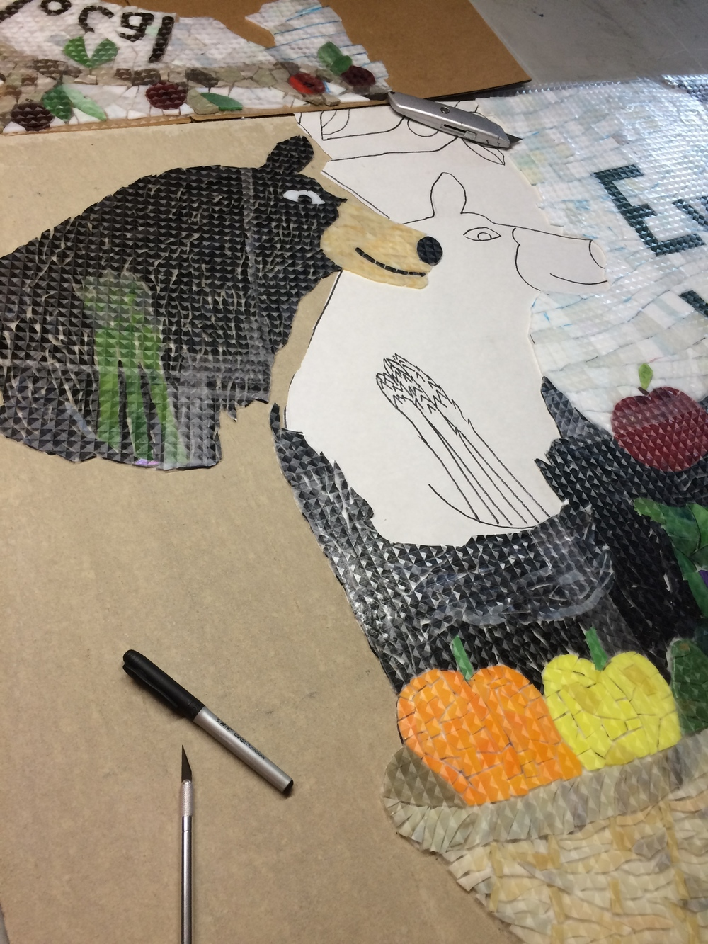 Cutting the mosaic into sections like puzzle pieces.