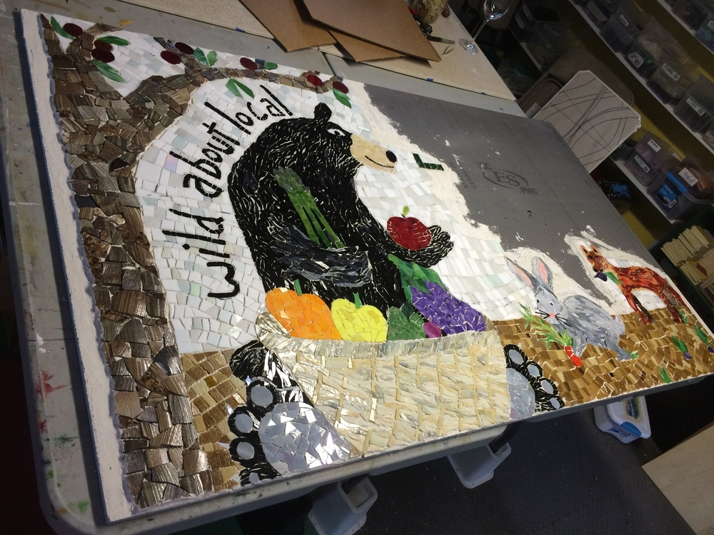 Attaching the sections of mosaic to the board.