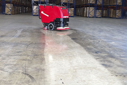 magnum-walk-behind-floor-scrubber-cleaning-and-polishing-concrete-floor-in-warehouse.jpg