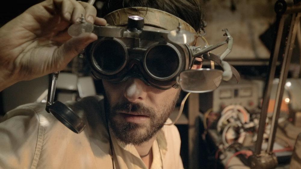 Frame do filme com o ator Ivo Müller na cena em que Marcos para o que está fazendo para observar Jamila, que acabara de chegar em sua oficina.