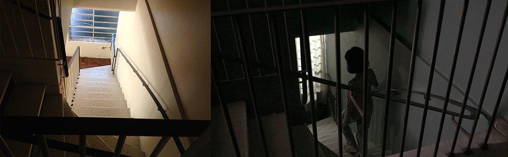 """As novas cores provocaram um clima mais soturno. Essa imagem é quase o ponto final de um planosequência, que mostra a protagonista caminhando pelo corredor e descendo as escadas. Desde o início eu sabia que esse era um dos enquadramentos necessários para o filme, no qual eu aproveitei as """"grades"""" do corrimão para fazer uma relação imagética subjetiva ao sentimento de aprisionamento da menina, dentro da casa."""