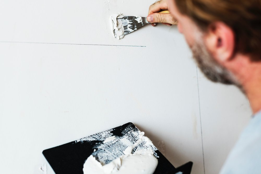 man patching wall in a real estate investment