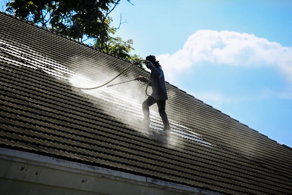 service man pressure washing roof in hillsboro