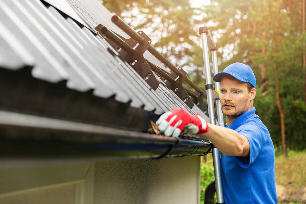 service man cleaning gutters on a hillsboro home