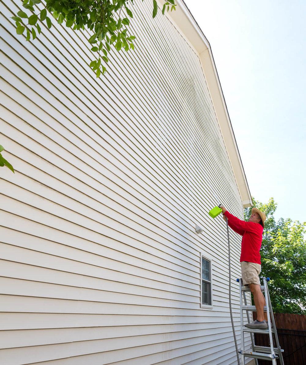 man spraying moss treatment onto siding of hillsboro home