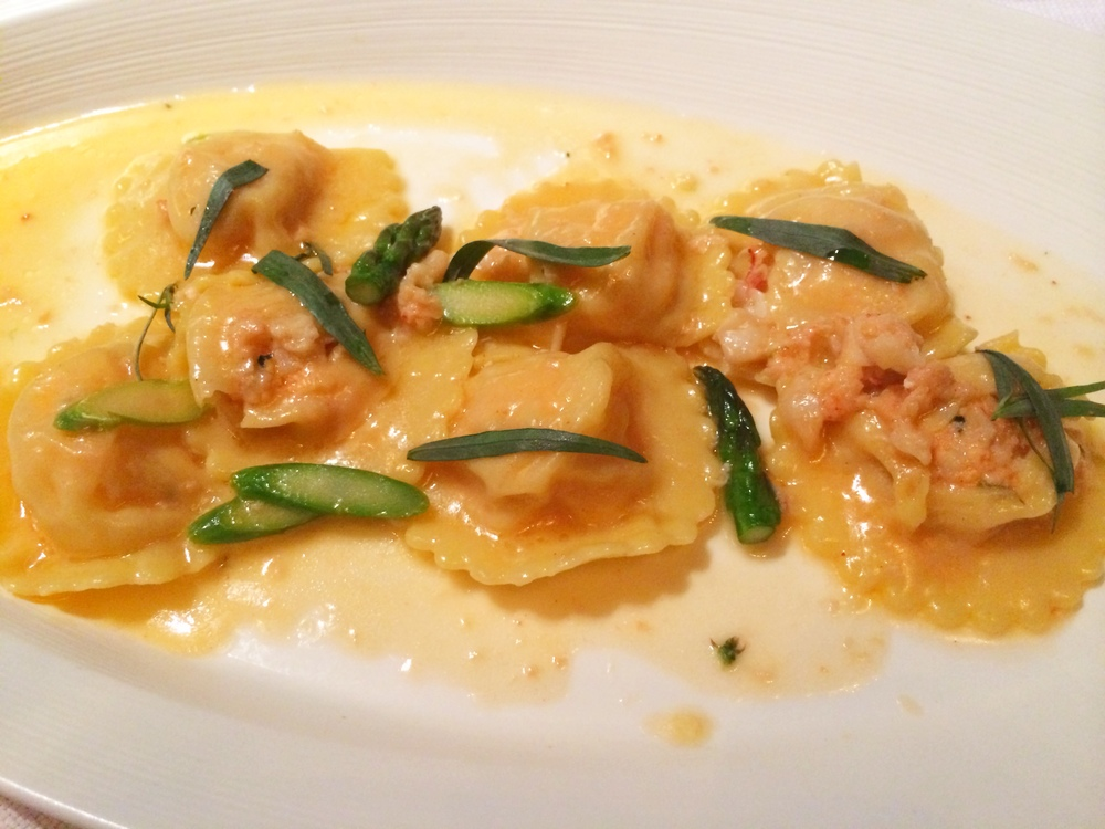 Lobster Ravioli with asparagus and garnished with tarragon.
