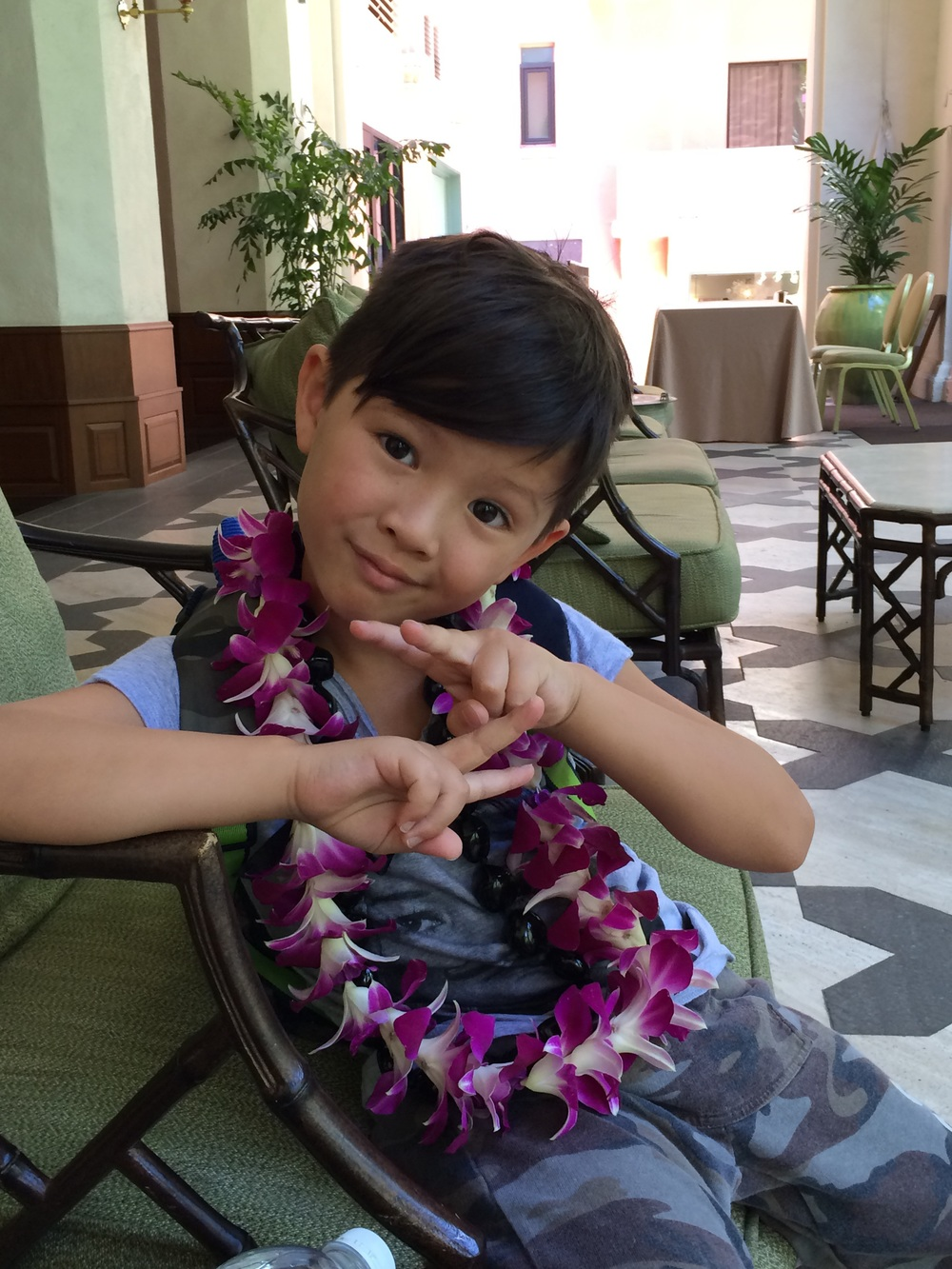 Hawaiian orchid lei in Hawaii but this really makes mesmile cause he's so goofy cute.