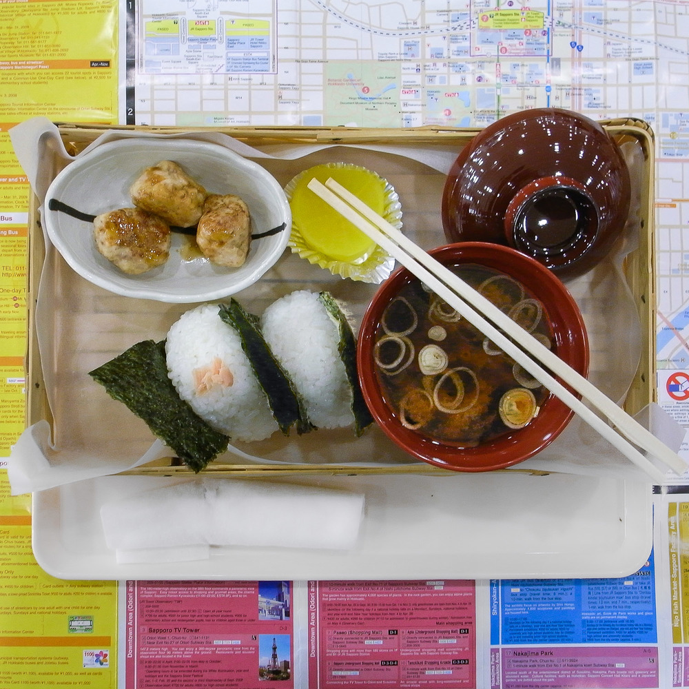The lunch tray at the train depot in Sapporo, Japan, was the Goldilocks of lunches, balanced in every regard—neither too small nor too big, slow yet fast and as indulgent as it was austere. It consisted of three small chicken meatballs, takuan pickled radish, miso soup and onigiri rice balls wrapped in nori, one with salmon, the other with an ume pickled plum. Photo by Natalia Osiatynska, taken in 2009 with the Ricoh GR Digital 2.