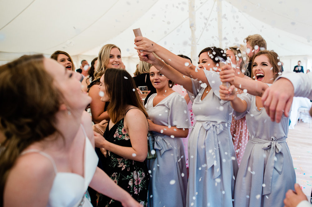 Bridesmaids throwing confetti over the bride on the dance floor