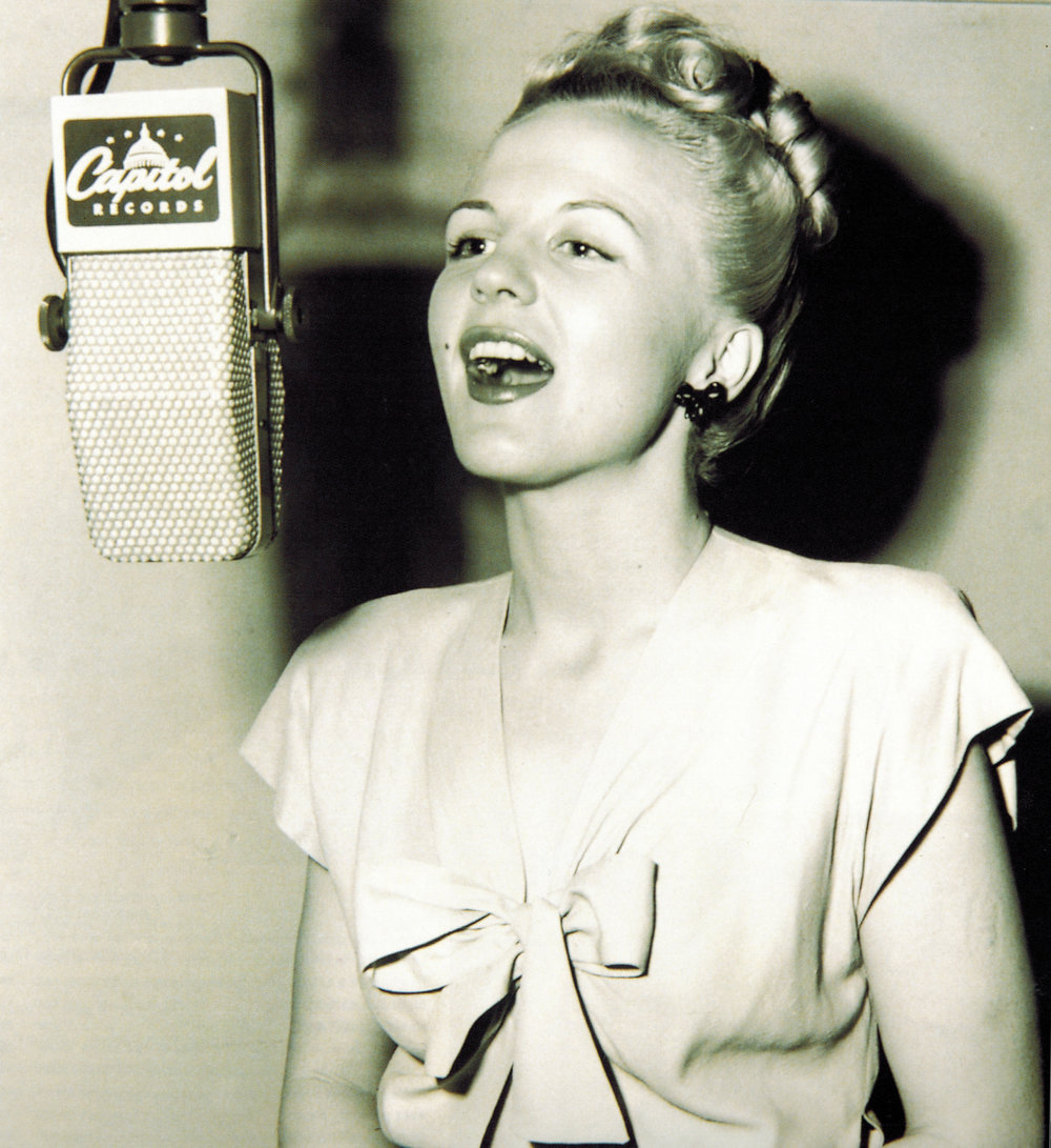 Peggy Lee at mic white dress (1920).jpg