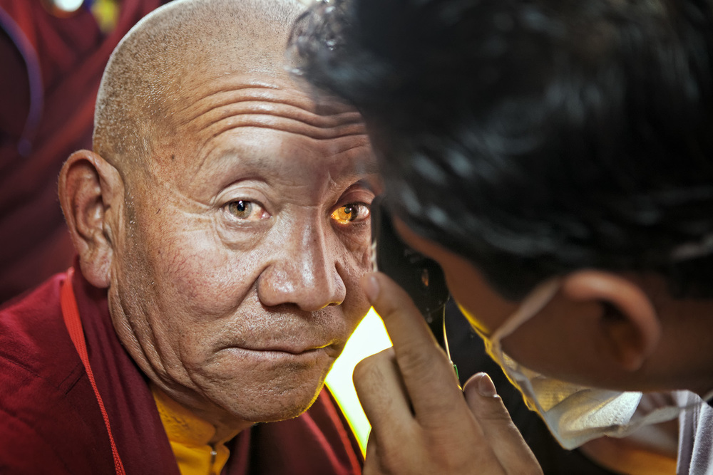 Monk having eyes checked, Hemis Monastery
