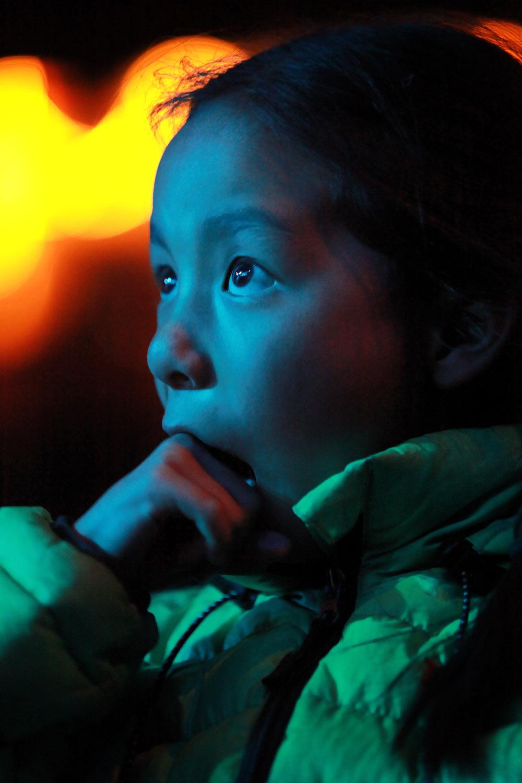Girl watching theatrical performance by Drukpa nuns, Hemis Monastery