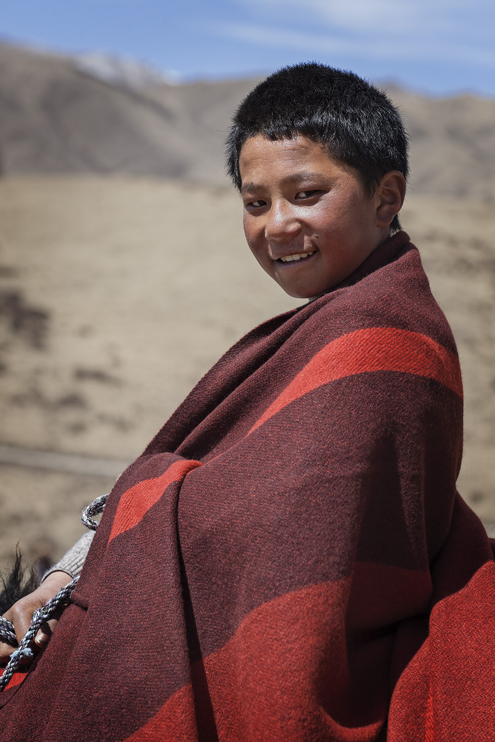 Boy riding young Yak - for Norlha Textiles in Amdo on the Tibetan Plateau
