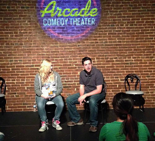Matt Holmes interviewing Shai, his partner from the audience at a Matt & performance at Arcade Comedy Theater in Pittsburgh.