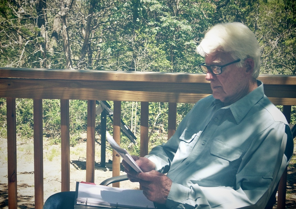Frank Evans reading brief on office deck.jpg