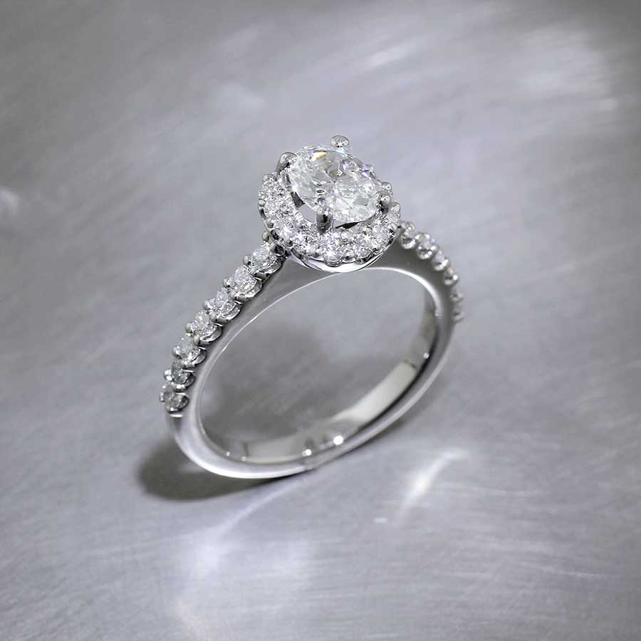 Style #22010504: Timeless Hand-Crafted Diamond Halo Ring Featuring Faceted Oval Diamond Center Stone, Platinum