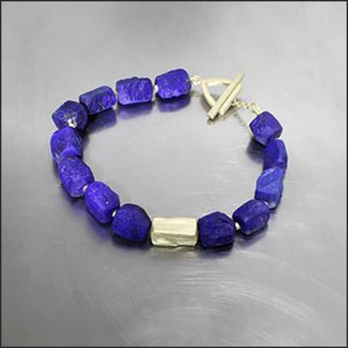 Style #23510044: Vibrant Lapis Lazuli Nugget Bracelet Featuring 18KY Triangular Toggle Clasp & Handmade Spacer Bead Stylized to Mirror the Lapis Nuggets