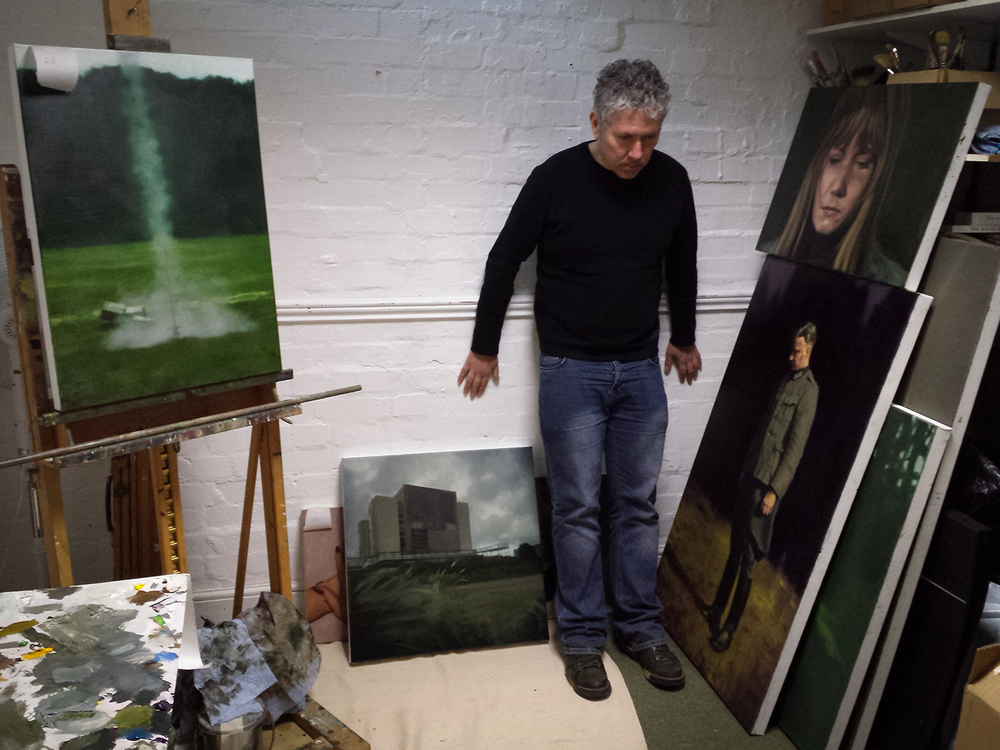 Artist, John Brennan, watches an imaginary cat in his Oxford studio