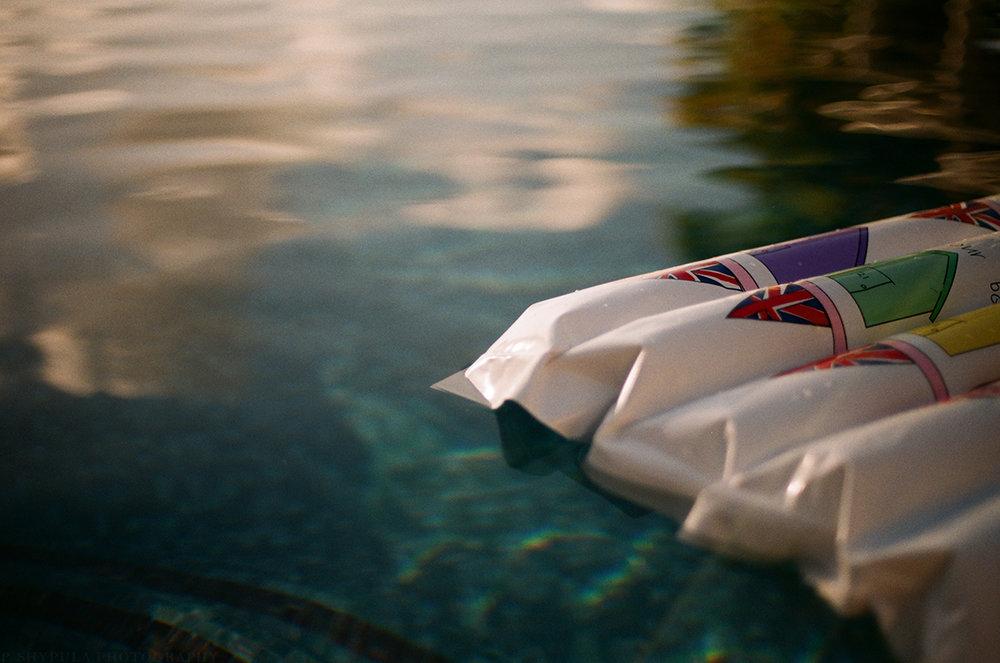 Featuring a pool float with a Daisy de Villeneuve design