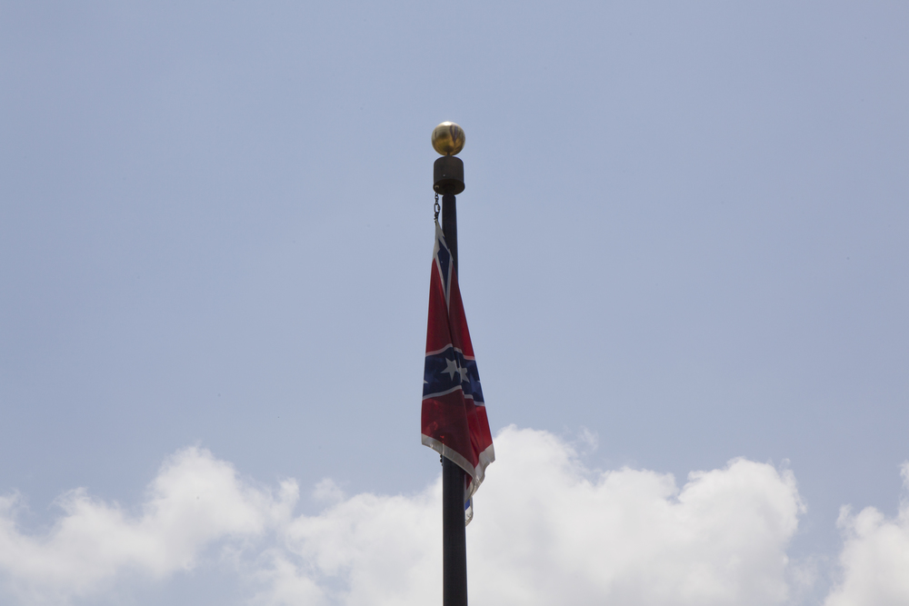 A Confederate Flag flying on South Carolina State House grounds as the casket containing the body of Senator Clementa Pinckney, murdered in a church on a basis of race, passes to enter the building