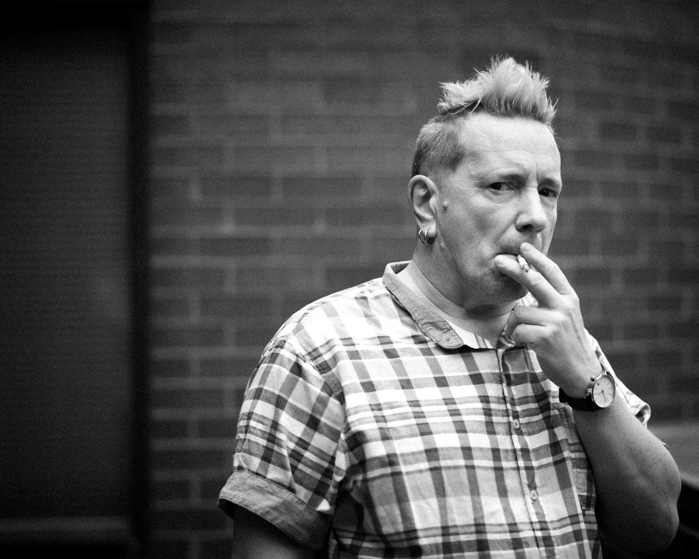 "John Lydon a.k.a. Johnny Rotten, the former lead singer of the Sex Pistols was in The Current's studios for a recording session with Public Image Ltd. Between takes John and his tour manager went for a cigarette break on our 4th floor balcony. I followed to just shoot some candid shots with the nice overcast light. After ignoring me for the first few minutes while I snapped away, Johnny gave me this intense look. I knew immediately I had ""the shot"" of the day, just an iconic F--- off glare from this classic punk rocker."