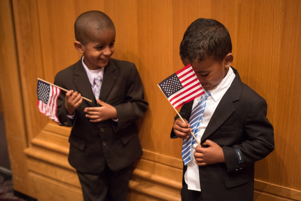 """Moti Terfassa and Burka Duvi play with American flags during a naturalization ceremony. Both were in attendance with their fathers and their mothers each became American citizens, emigrating form Ethiopia, The ceremony at the Minneapolis Convention Center was the largest ever held in Minnesota, with 1580 immigrants from 100 countries becoming citizens. (Sept. 6th, 2012. Minneapolis, MN) MPR Photo/Nate Ryan"" The main reason I went down to the Convention Center yesterday morning was to capture 89.3 The Current's Mark Wheat become an American citizen. The atmosphere of the event was full of excitement with room full of people all pledging allegiance to the United States as they became citizens. After more than 20 years in the US, Mark became an American citizen just in time to be able to vote this fall. See more photos and read Luke Taylor's interview with Mark about why he decided to finally become a citizen: http://minnesota.publicradio.org/display/web/2012/09/06/citizen-mark"