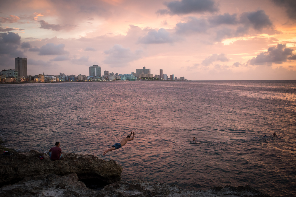 Dusk along the Malecon, men swim and dive into the ocean near the entrance to the mouth of the Bay of Havana at sunset