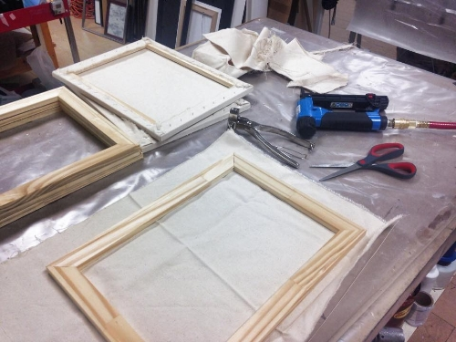 We then stretch and staple the canvas around the backside of the frame -- tight enough to prevent wrinkles, but not too tight, to prevent buckling!
