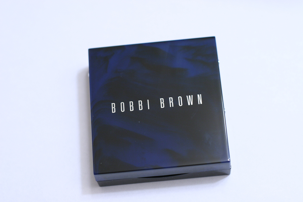 Bpbbi Brown's Navy and Nude Palette is housed in a square plastic compact in a beautiful blue tortoiseshell. Stylish and portable! It also comes with a mirror.