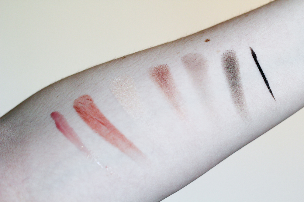 Swatches of Make Up For Ever's Give In To Me Set (left to right): Lab Shine Lip Gloss in D14; Rouge Artist Natural Lipstick in N4; Artist Shadows in I-514, ME-612, S-556 and I-628; and Graphic Liner. (Missing: Smoky Extravagant Mascara.)