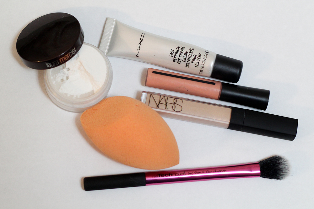 Products I use daily to cover my under-eye circles, clockwise from the top: MAC Fast Response Eye Cream, Giorgio Armani Master Corrector, NARS Radiant Creamy Concealer, Real Techniques Miracle Complexion Sponge, Real Techniques Setting Brush, and Laura Mercier Secret Brightening Powder.