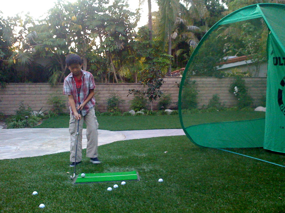 Hitting golf balls in the back yard with the boy.