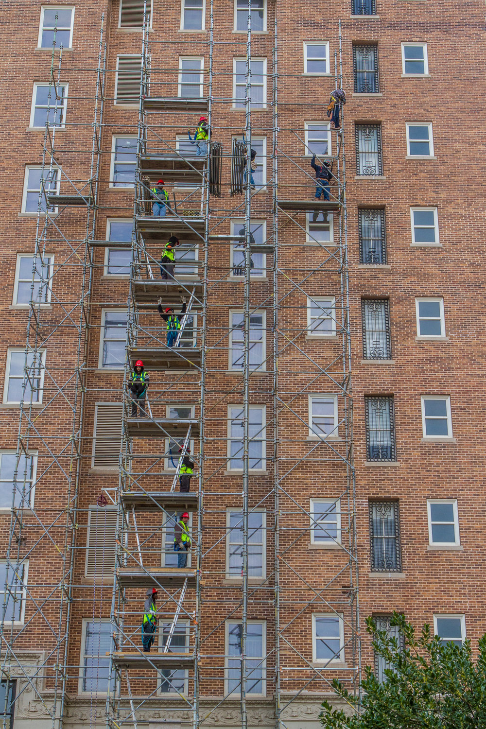 Workers with Safway construction form a relay line to assemble scaffolding outside the Skervin Hotel in Oklahoma City.