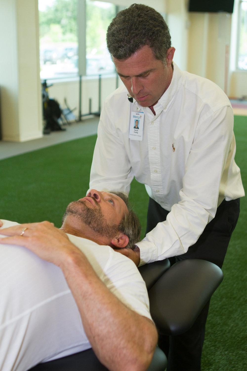 David Husling, Director of Sports Performance at  Mercy Fitness Center in Edmond, Oklahoma assists his client, Gary Brooks, with some stretches and exercises.
