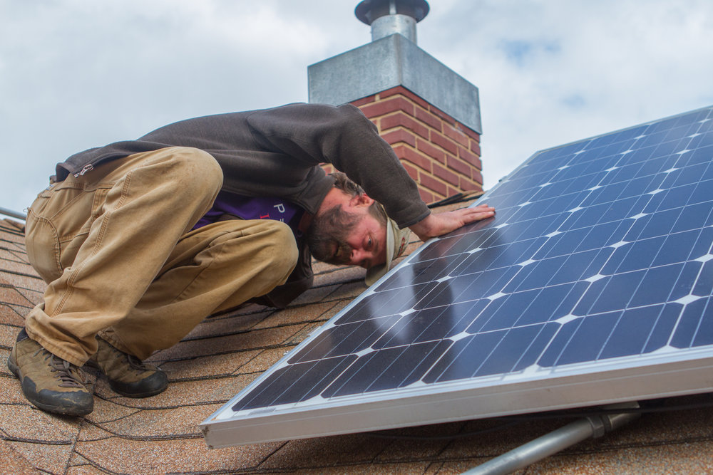 Tod Hanley, project manager for Delta Energy & Design, inspects a residential solar panel installation in Norman, Oklahoma.