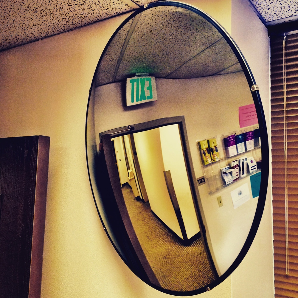A wide angle mirror in the waiting room at the probation office
