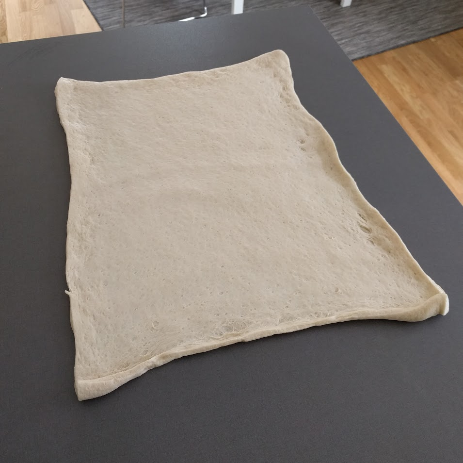 3. Lägg ut degen på bänken och dra lite i kanterna så den blir större.