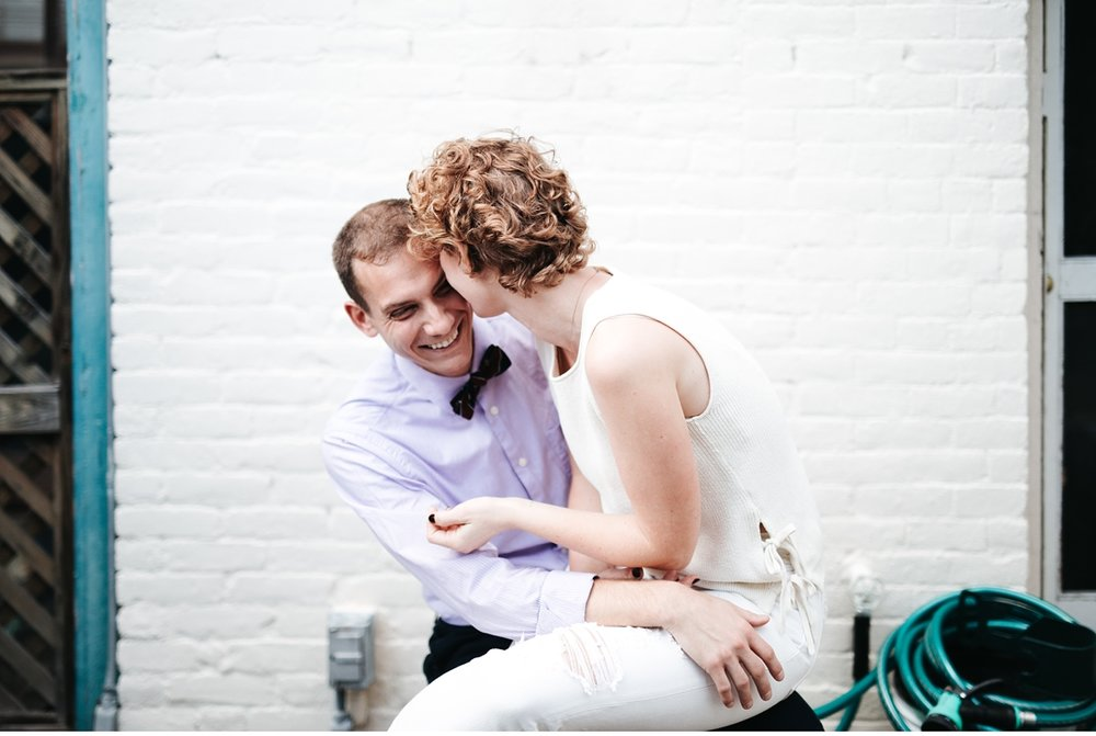 Couple laughing in Boston apartment during engagement session