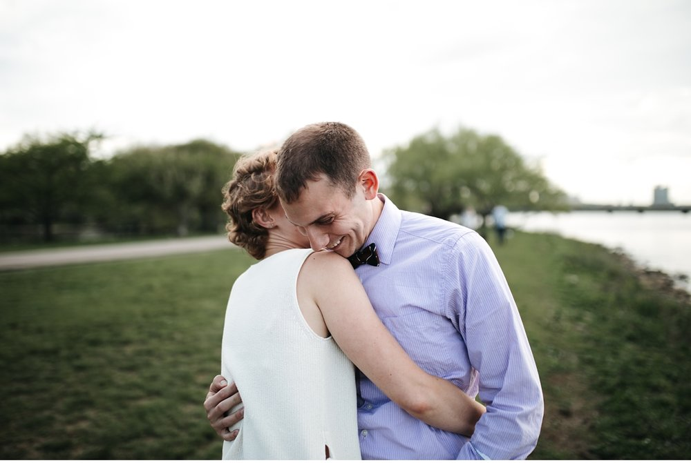 Hugging couple in riverside park, Boston engagement session