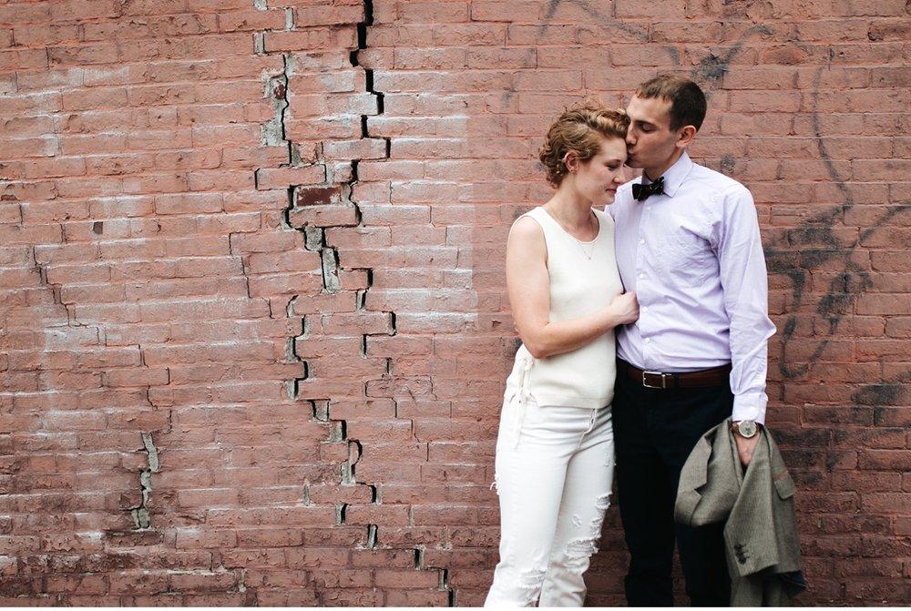 Man kissing financè's cheek against brick wall in Boston MA