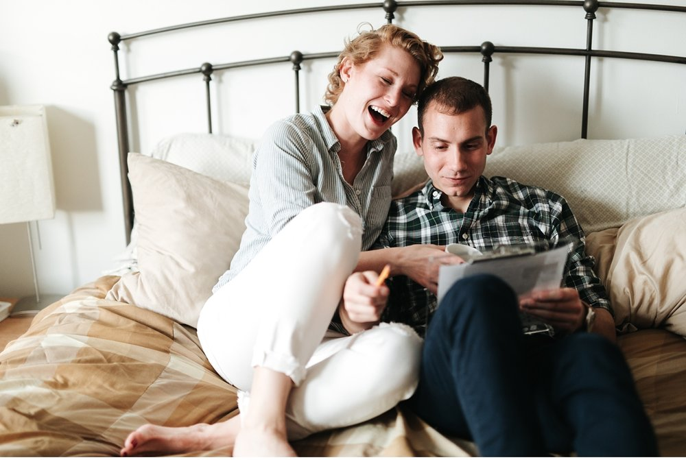 couple doing crossword together during in home engagement session
