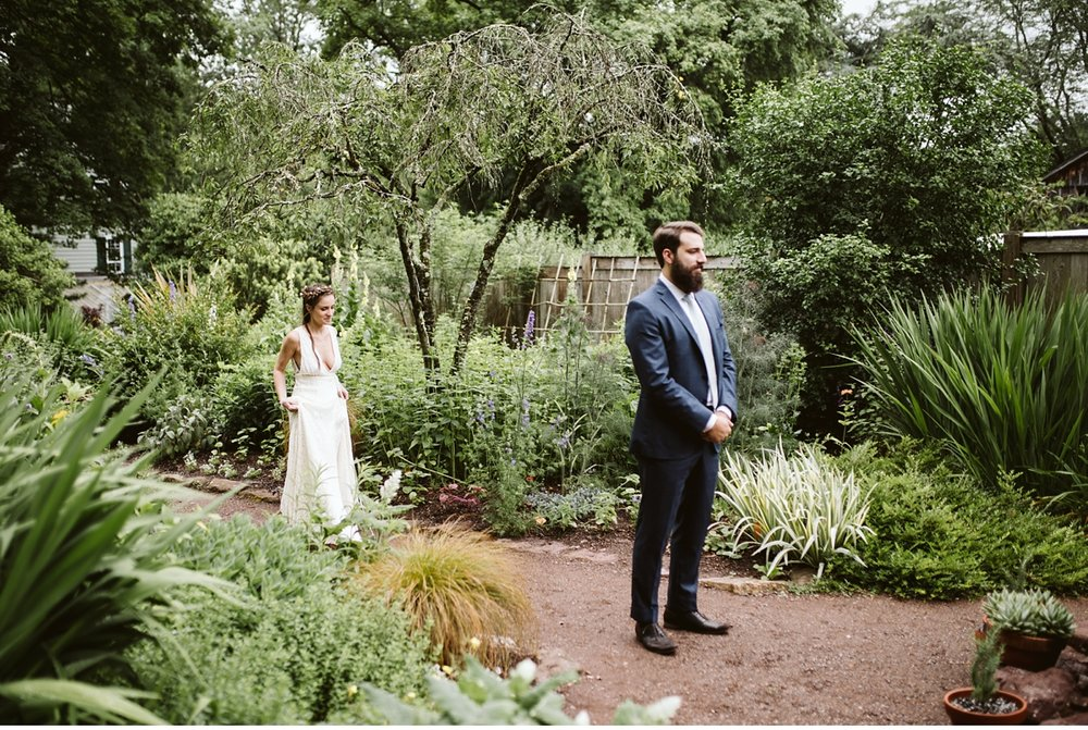 Bride walks towards groom for first look in Willowwood Arboretum