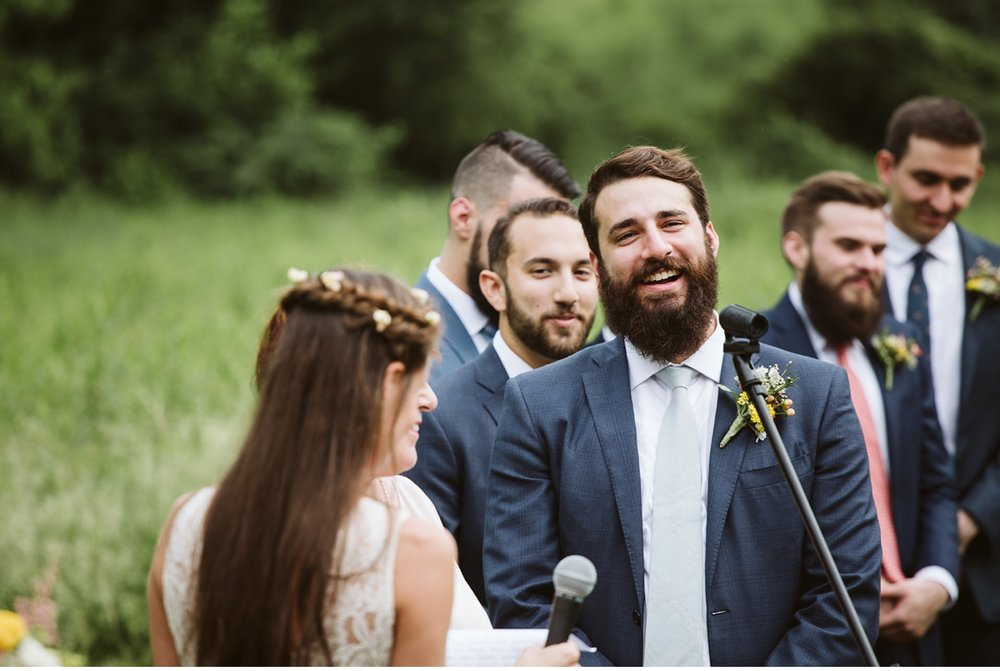 Groom laughing during ceremony at Willowwood Arboretum